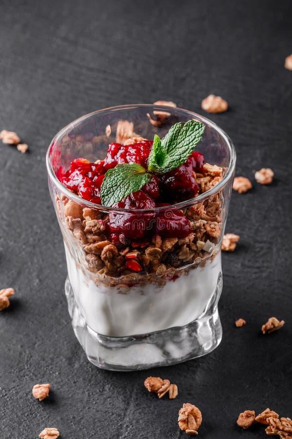 Granola delicioso com iogurte e cereja no vidro no fundo preto Ingredientes saudáveis do pequeno almoço Comer limpo imagens de stock