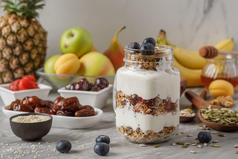 Granola e yogurt e frutti sulla guarnizione in vetro sulla tavola di pietra, alimento sano per il concetto di dieta fotografia stock libera da diritti