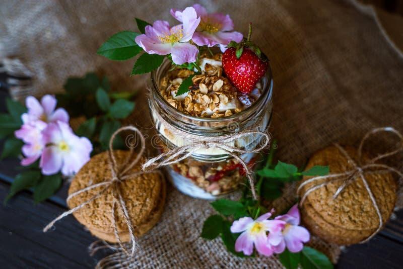 Granola in een kruik en bloemen op een houten lijst stock fotografie