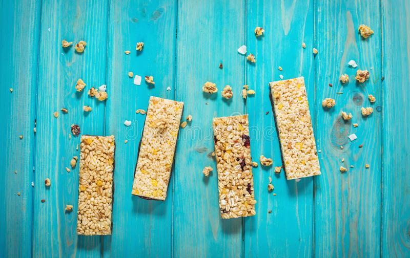 Granola energy bars with oatmeal, almond, dry cranberry. Healthy snack on blue wood background royalty free stock image