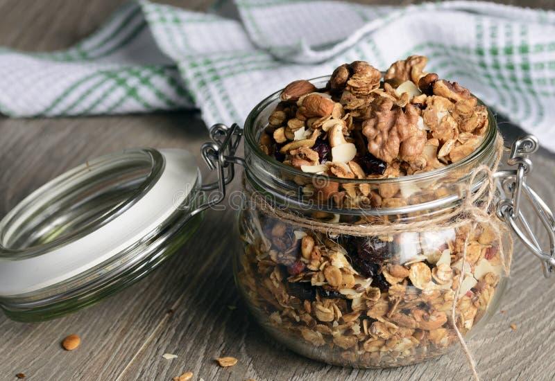 Granola faite maison dans le pot en verre ouvert sur le fond en bois rustique images stock