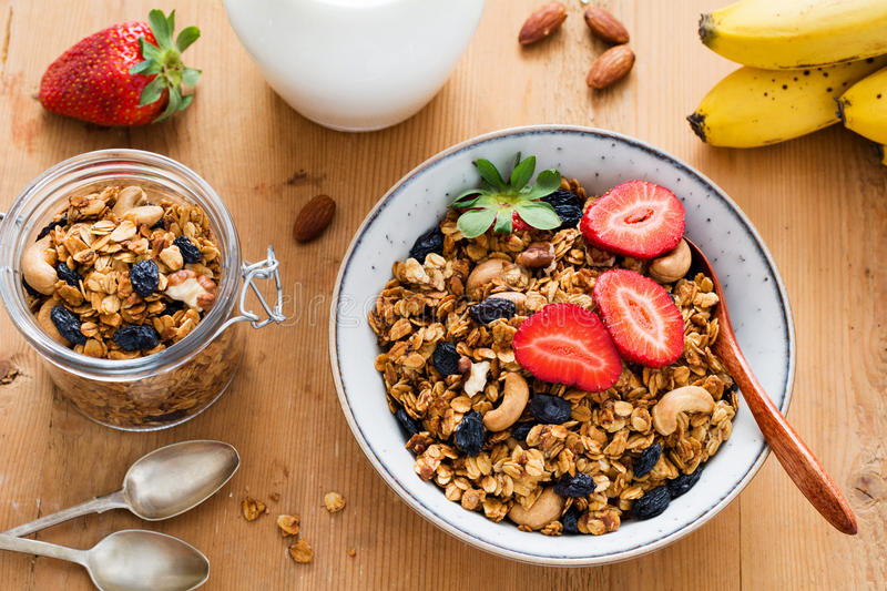 Granola, fresh fruits and berries for healthy diet breakfast. Granola, milk and fruits. Tasty and healthy breakfast: bowl of granola with fresh strawberries, jug royalty free stock photography