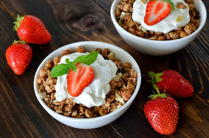 Granola. With fresh strawberry in a white bowl on a dark rustic desk royalty free stock photo