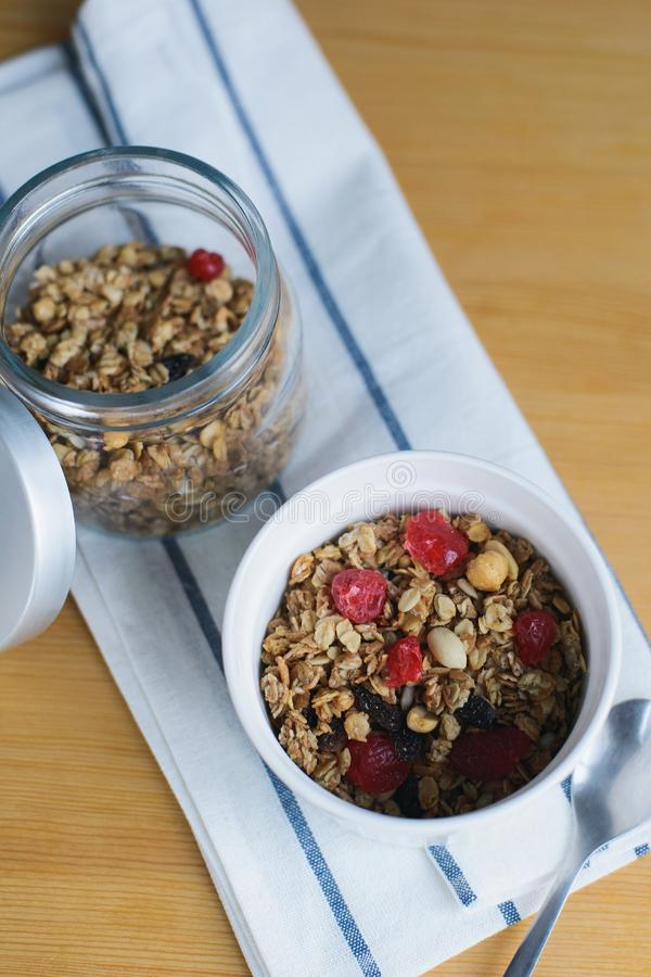 Granola with fried oatmeal flakes, hazelnuts, peanuts, dried raisins and cherries. In glass and white bowl on textile napkin on wooden table, close up top view stock photography