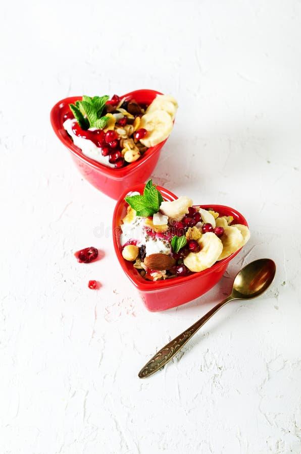 Granola hecho en casa con el yogur en placa roja del corazón en la tabla blanca Espacio libre del desayuno romántico para su text foto de archivo