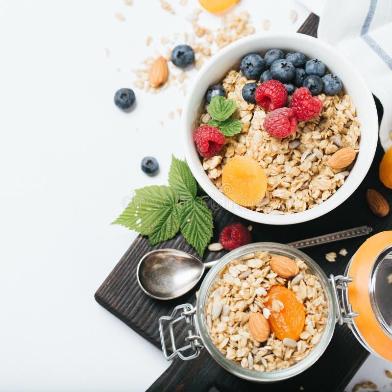 Granola hecho en casa con frutos secos y bayas en el fondo blanco foto de archivo libre de regalías