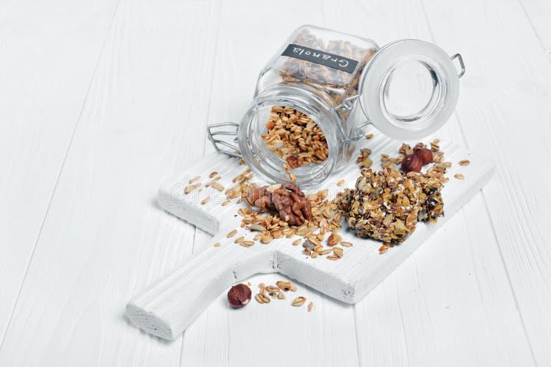Granola hecho en casa del desayuno sano con las nueces y las semillas de girasol en barra de cristal abierta del tarro y de energ foto de archivo libre de regalías