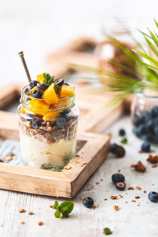 Granola libre del gluten con el yogur, los arándanos y Mange del coco en el tarro para el desayuno sano imagen de archivo