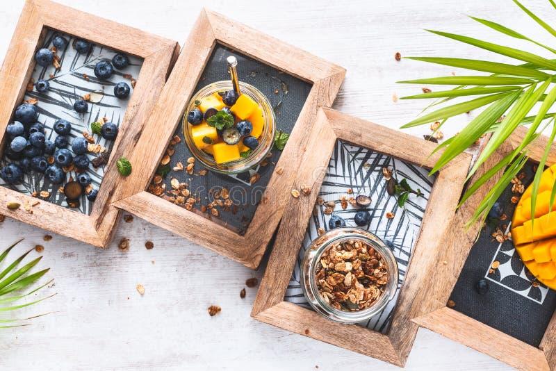 Granola libre del gluten con el yogur, los arándanos y Mange del coco en el tarro para el desayuno sano foto de archivo