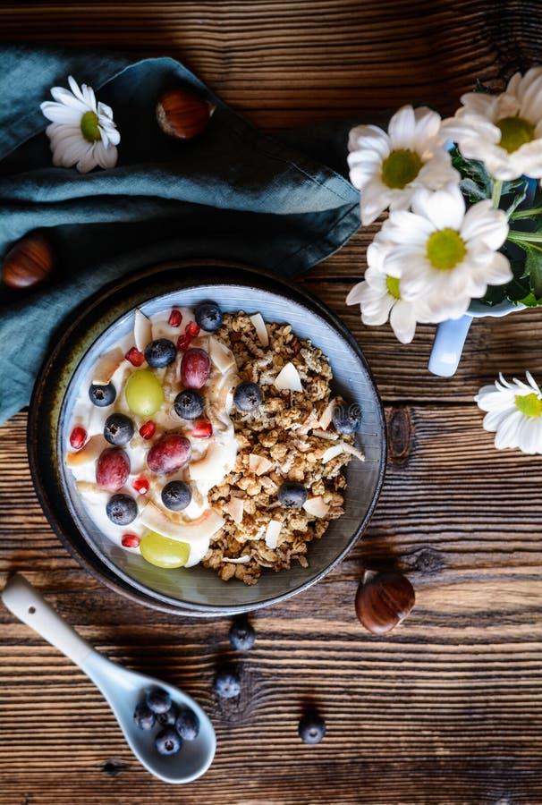 Granola med yoghurt, druvor, blåbär, kokosnötchiper och kastanjebrun puré arkivbild