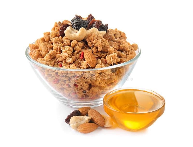 Granola met droge vruchten en noten in kom en zoete honing op witte achtergrond stock afbeelding