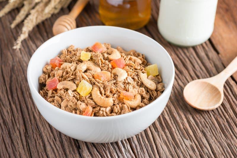 Granola met droge vruchten en noten in witte kom stock afbeeldingen