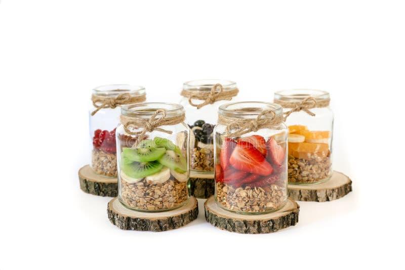 Granola met plakken van verschillende verse die vruchten in kruiken op witte achtergrond worden geïsoleerd stock foto