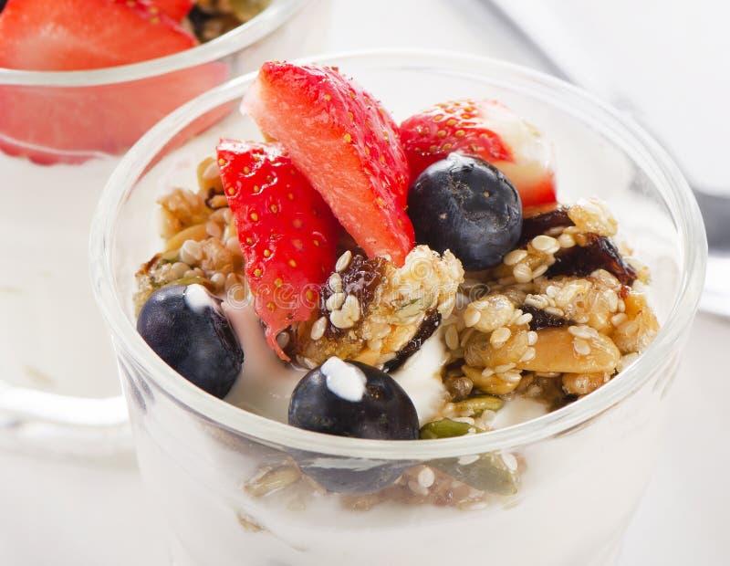 Granola met yoghurt en bessen in glas stock fotografie