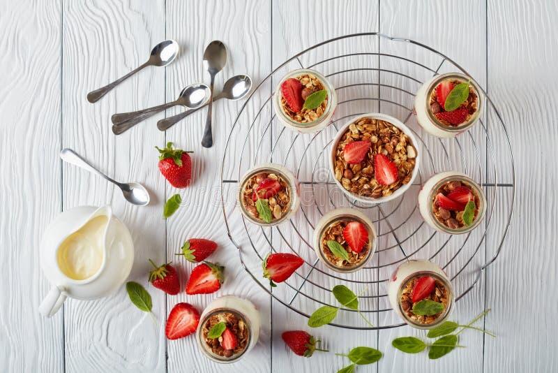 Granola met yoghurt in glaskruiken stock fotografie