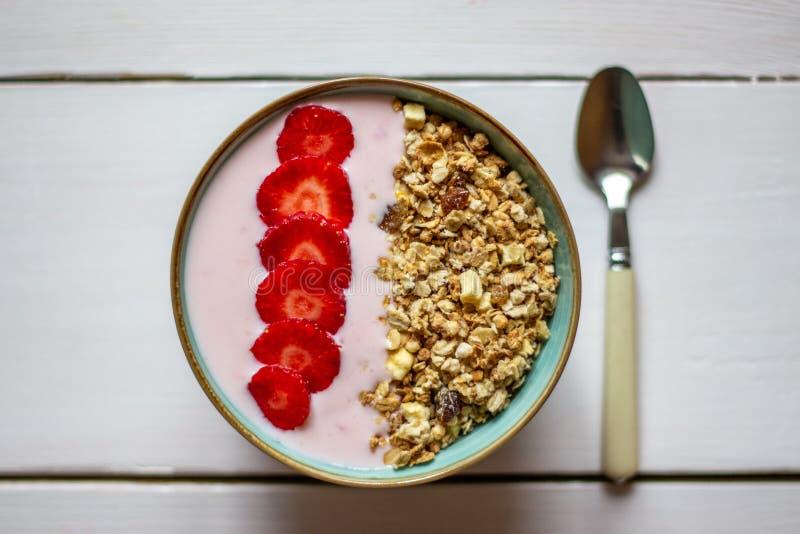 Granola mit Erdbeeren auf einem wei?en h?lzernen Hintergrund stockbilder