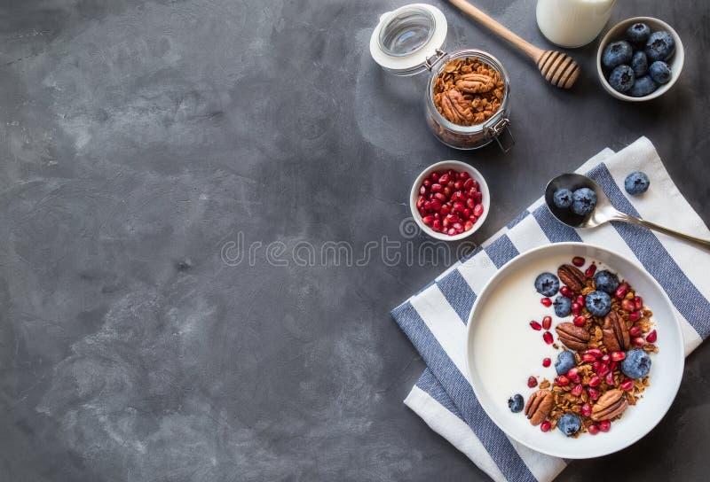 Granola, muesli con las semillas de la granada, ar?ndanos y yogur fotos de archivo libres de regalías
