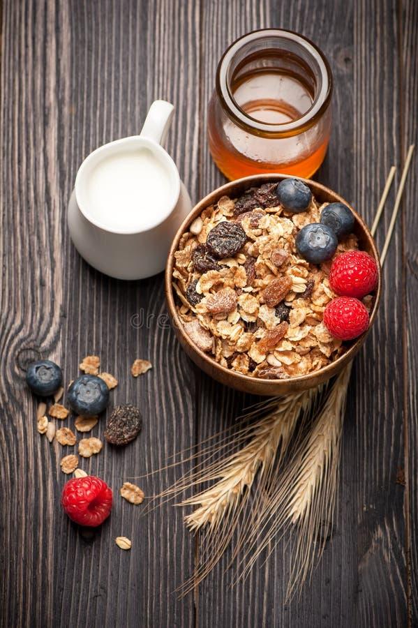 Granola muesli with honey, berries and milk royalty free stock images