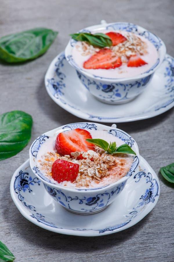 Granola, muesli met aardbeien en de yoghurt verfraaien met munt in ceramische kommen op houten grijze achtergrond stock afbeeldingen