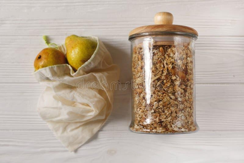 Granola nelle borse naturali di eco e di vetro con i frutti, disposizione piana Pla fotografia stock libera da diritti