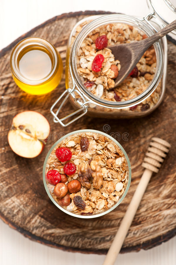 Granola with nuts, dried fruit and honey on wooden background. Granola with dried fruits, honey and nuts. See series stock photos