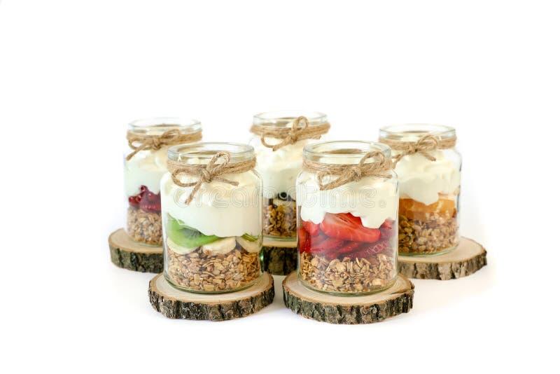 Granola, plakken van verschillende verse die vruchten, yoghurt in kruiken op witte achtergrond worden geïsoleerd royalty-vrije stock afbeeldingen