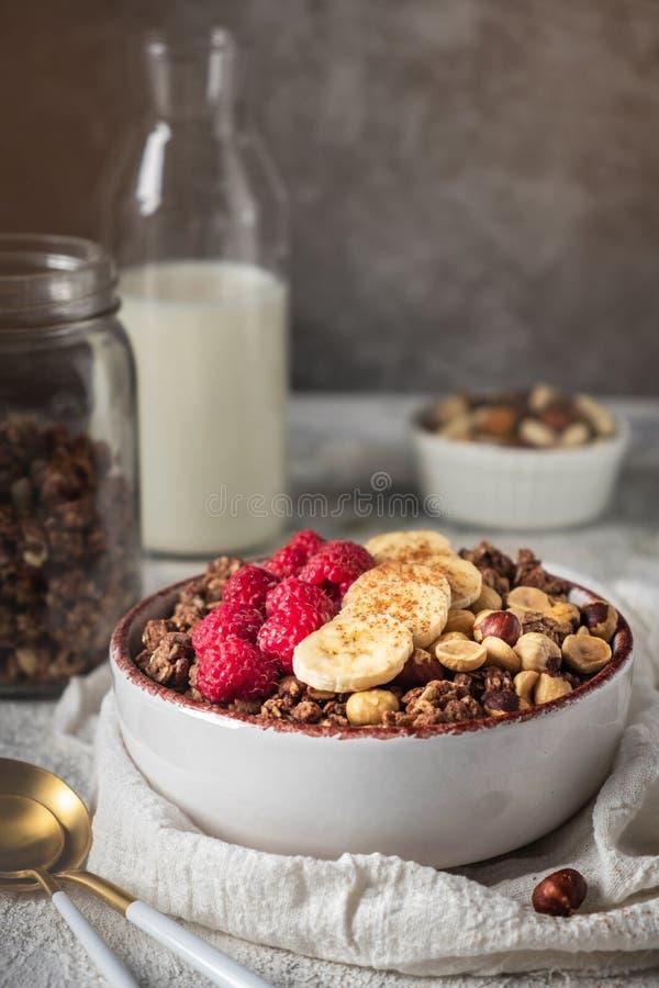 Granola saine de petit déjeuner dans un plat avec les écrous, la banane et les framboises image libre de droits