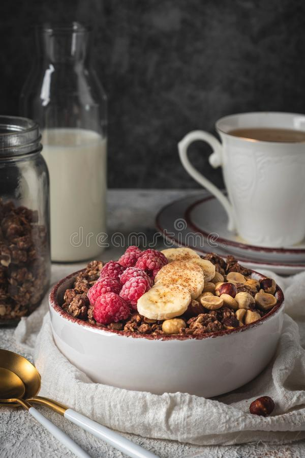 Granola saine de petit déjeuner dans un plat avec les écrous, la banane et les framboises photographie stock libre de droits