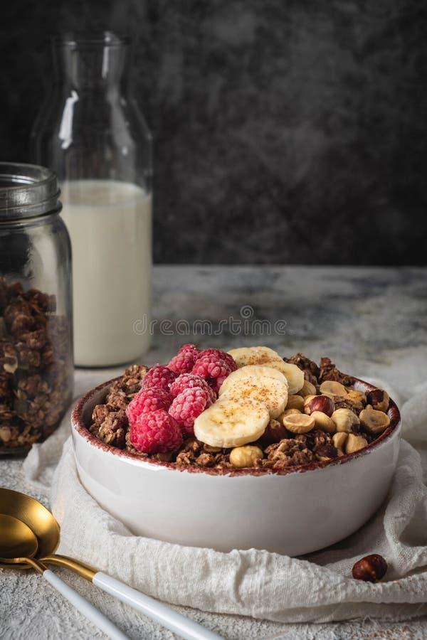 Granola saine de petit déjeuner dans un plat avec les écrous, la banane et les framboises images stock