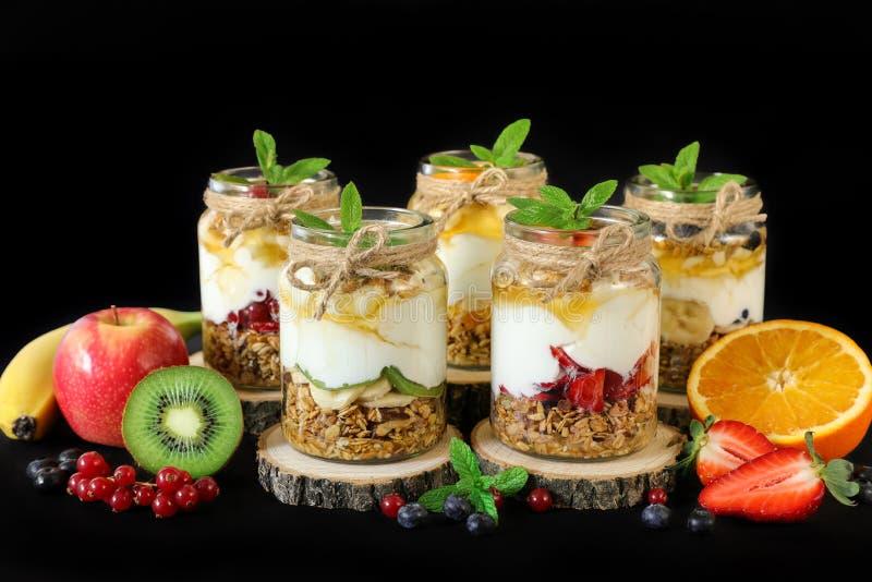 Granola, skivor av olika nya frukter och bär, yoghurt, honung i krus som isoleras på svart bakgrund arkivfoto