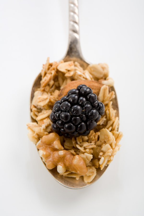 Granola Spoonful. Spoonful of Granola Cereal with Raspberry royalty free stock photo