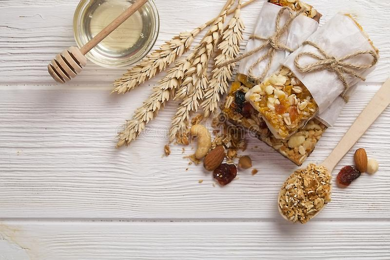 Granola superfood with almond and cashew nuts, dry fruits, raisins cherry in the ceramic jar on the white wooden table, top view, royalty free stock photo