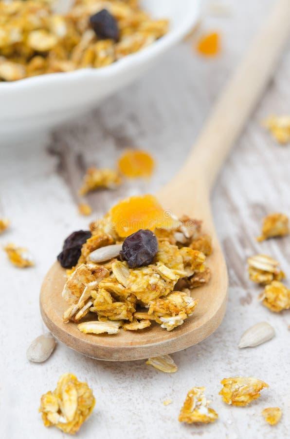 Granola van de pompoen met gedroogd fruit en zaden in een lepelclose-up stock afbeelding