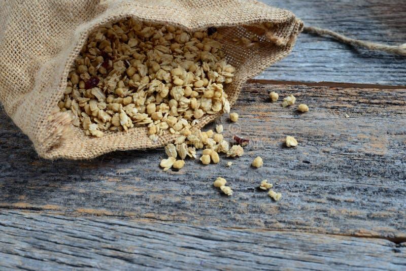 Granola w Burlap Workowy Rozlewać na Drewnianym tle zdjęcie stock
