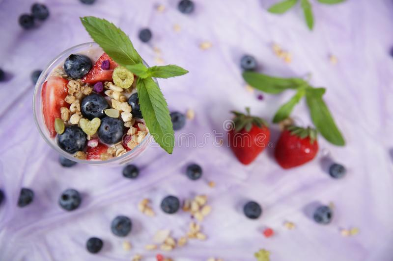 Granola yogurt parfait with fresh blueberries and strawberries on a light lilac background. The concept of healthy eating. Top vie royalty free stock image