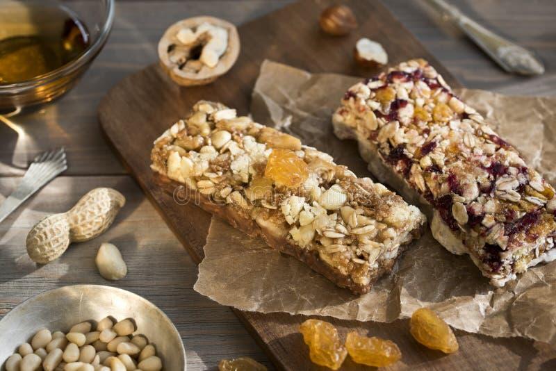 Granolabars met noten en droge vruchten en honing op houten snack als achtergrond voor gezonde nog levend stock afbeelding