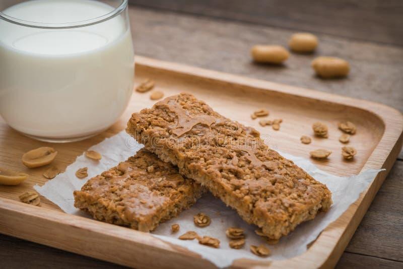 Granolabars op houten plaat en glas melk stock afbeeldingen
