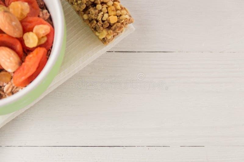 Granolagetreideflocken mit Trockenfrüchten, Nüsse in der grünen Schüssel auf weißem Holztisch Draufsicht mit Copyspace stockbild