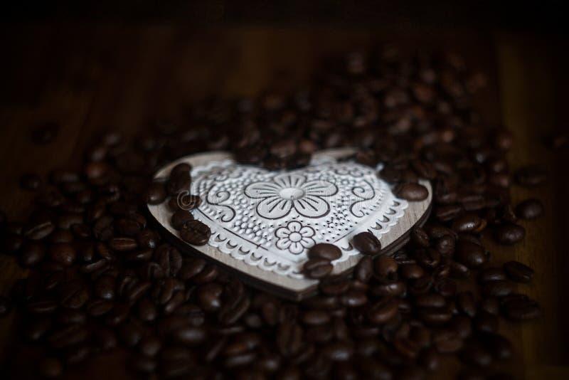 Granos blancos del corazón y de café en una tabla de madera foto de archivo libre de regalías