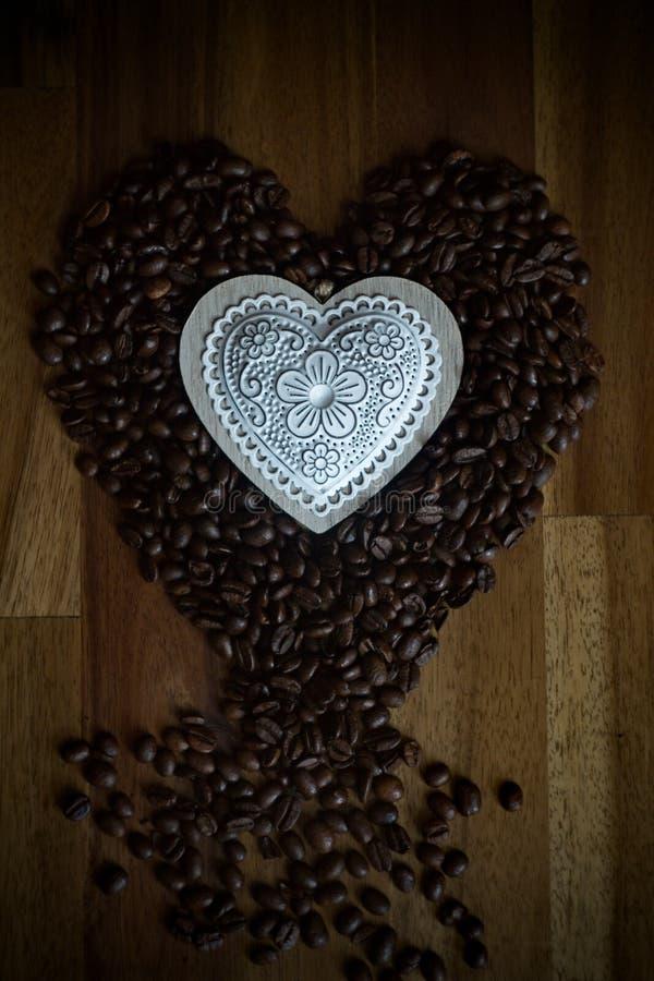Granos blancos del corazón y de café en una tabla de madera fotografía de archivo libre de regalías