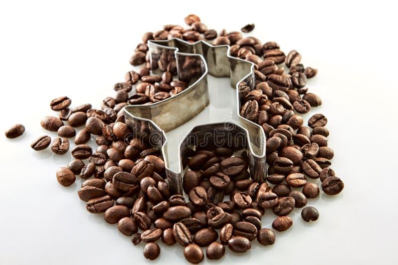 Granos de café alrededor de una forma de los ciervos aislados en blanco fotos de archivo