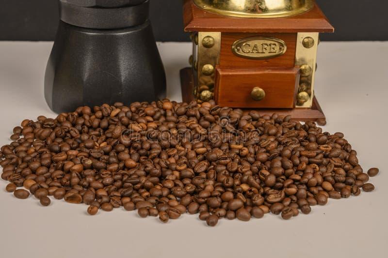 Granos de café asados en el fondo blanco con la amoladora de café y el fabricante de café imagen de archivo libre de regalías