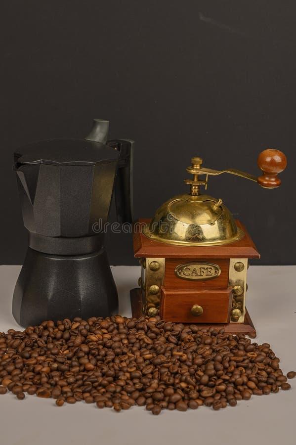Granos de café asados en el fondo blanco con la amoladora de café y el fabricante de café imagenes de archivo