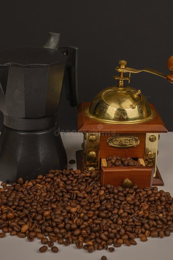Granos de café asados en el fondo blanco con la amoladora de café y el fabricante de café fotografía de archivo libre de regalías