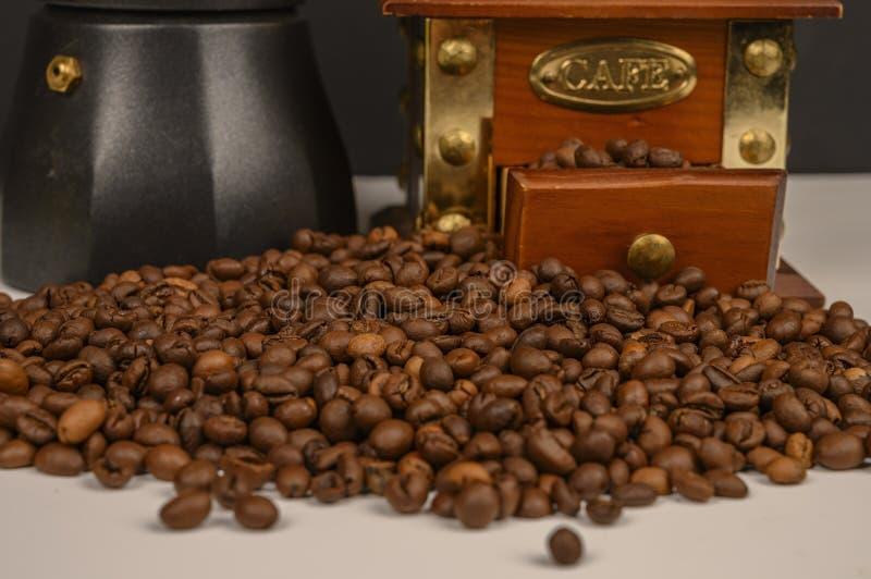 Granos de café asados en el fondo blanco con la amoladora de café y el fabricante de café imágenes de archivo libres de regalías