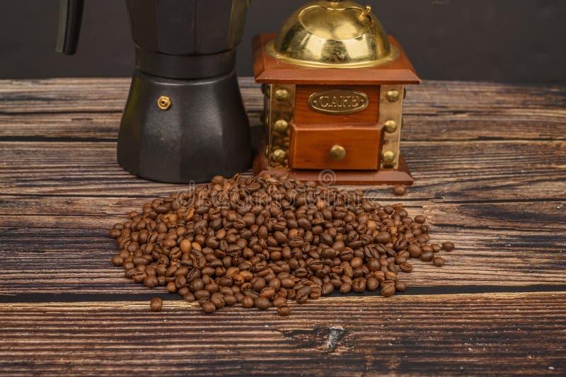Granos de café asados en el fondo de una tabla de madera con una amoladora de café y un fabricante de café imagen de archivo