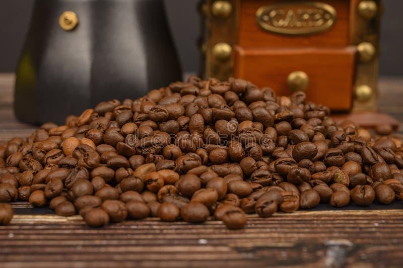 Granos de café asados en el fondo de una tabla de madera con una amoladora de café y un fabricante de café imágenes de archivo libres de regalías