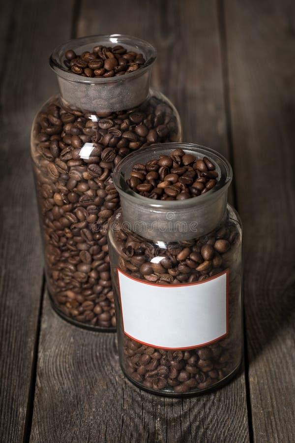 Granos de café asados en un tarro cristal en el fondo de madera fotografía de archivo libre de regalías