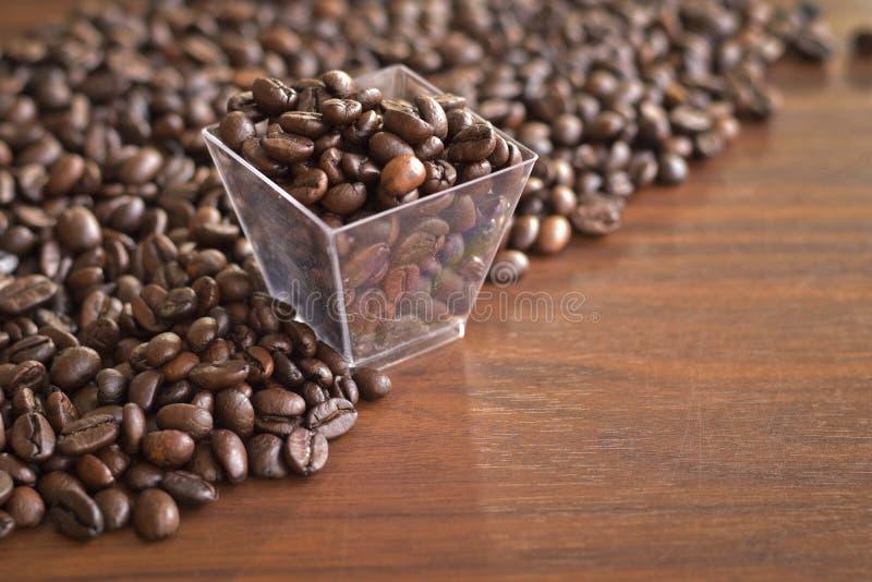 Granos de café asados en una caja plástica y un montón viejos de la PU del café fotografía de archivo