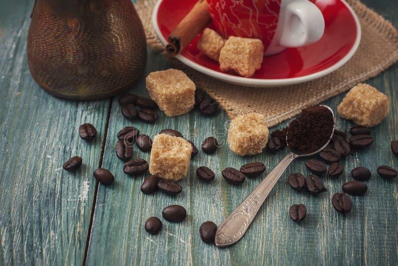 Granos de café, azúcar y taza de café roja en fondo de madera fotos de archivo